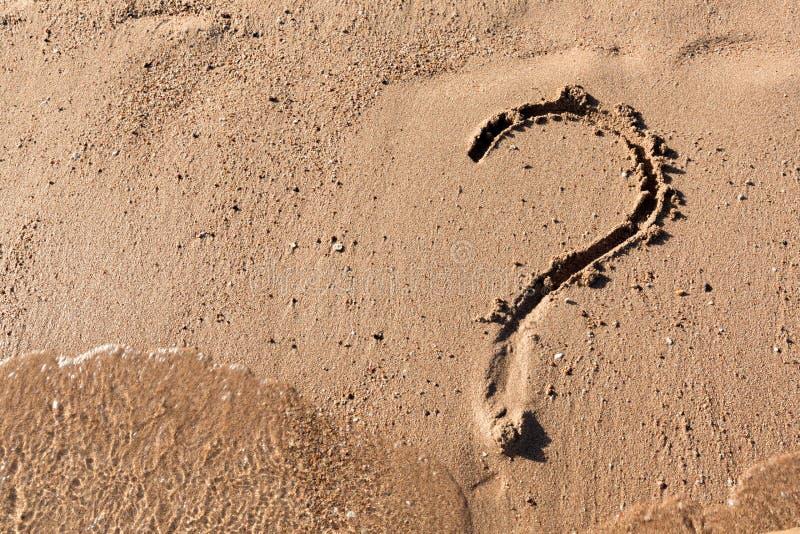 Le point d'interrogation se connectent la plage de sable pr?s de la mer Concept de dilemme, de r?ponse et de question photos libres de droits