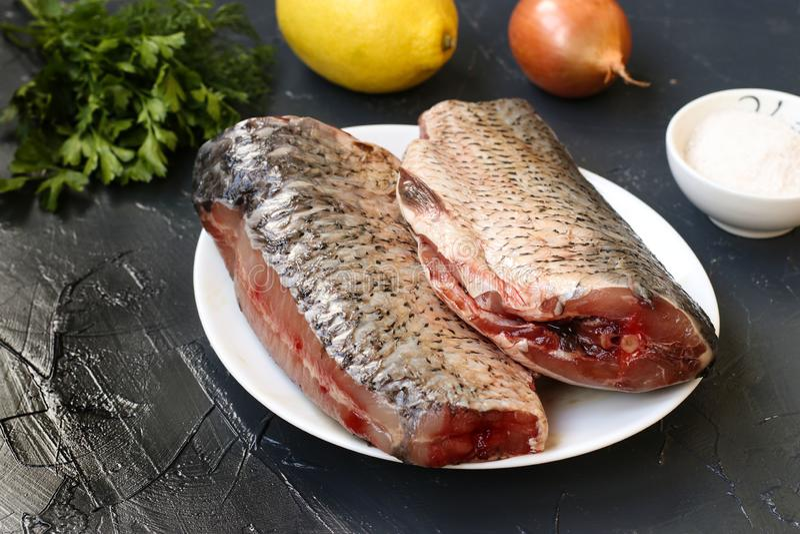 Le poisson cru est situé sur un plat sur un fond foncé photo stock