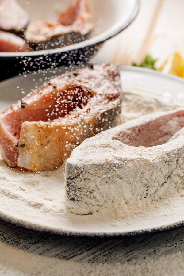 Le poisson frais et cru de carpe coupe en tranches le sel chevronné et des épices de mer, panés dans la farine et la chapelure photographie stock libre de droits