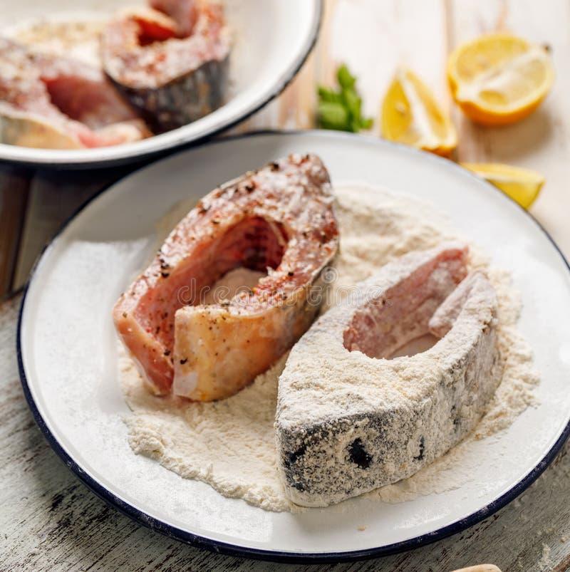 Le poisson frais et cru de carpe coupe en tranches le sel chevronné et des épices de mer, panés dans la farine et la chapelure photos stock