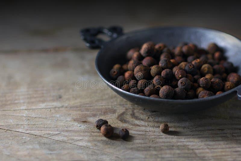 Le poivre de Jamaïque ou le poivre anglais, les baies sèches entières dans un métal roulent image libre de droits