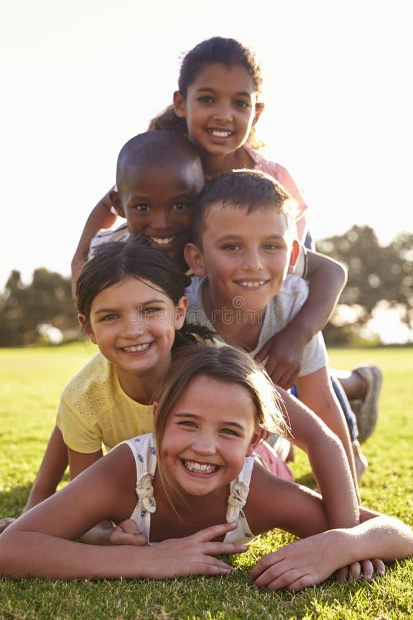 Le pojkar och flickor som ligger i en hög på gräs i sommar arkivbilder