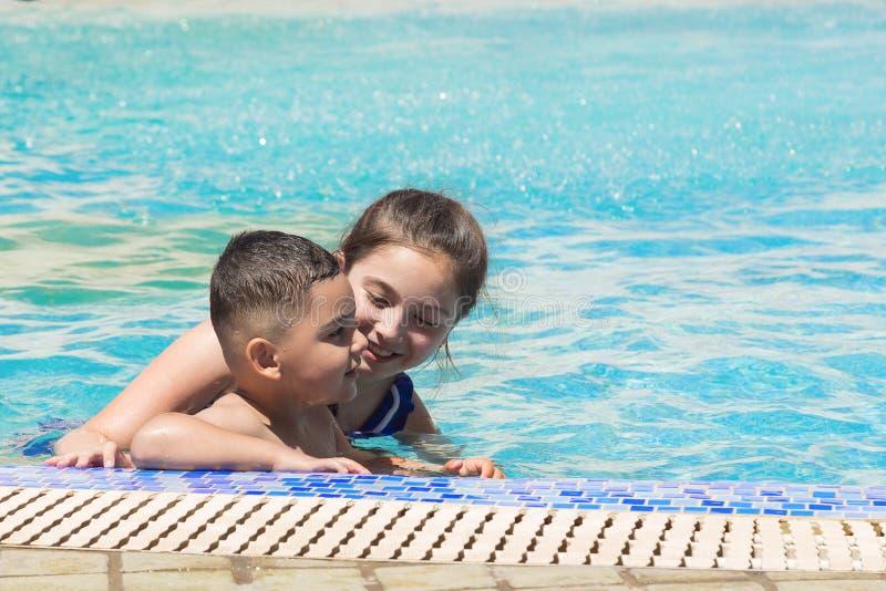 Le pojke- och liten flickasimning i pöl i aquapark Resa resväskan med seascapeinsida Utrymme för text royaltyfria foton