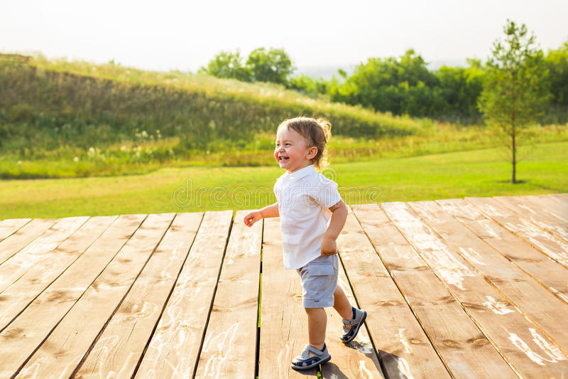 Le pojken i fältet på den soliga sommarmorgonen Pojke i den vita skjortan Familjen reser, barnet körde lyckligt runt om fotografering för bildbyråer