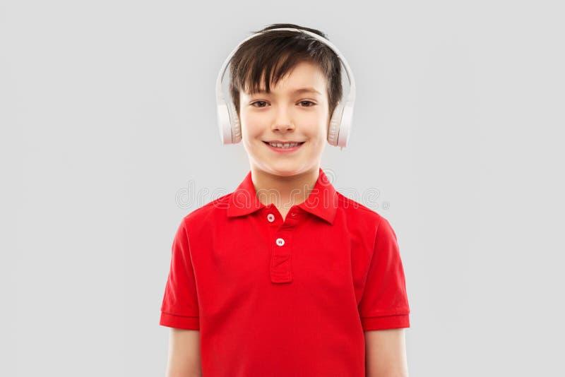 Le pojken i hörlurar som lyssnar till musik royaltyfria bilder