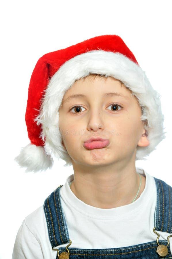 Le pojken i röd hatt för jultomten arkivbild