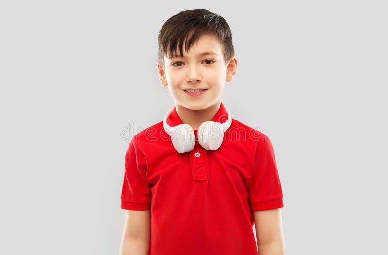 Le pojken i röd t-skjorta med hörlurar på hals arkivfoton
