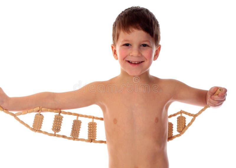 Le pojken med den manuella trämassören som isoleras på vit arkivfoton