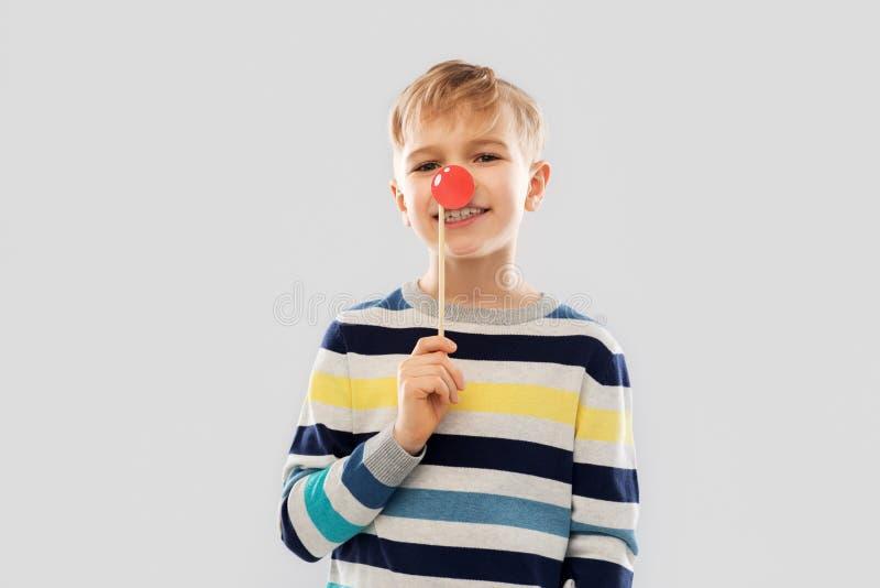 Le pojken med den röda stöttan för clownnäsparti fotografering för bildbyråer