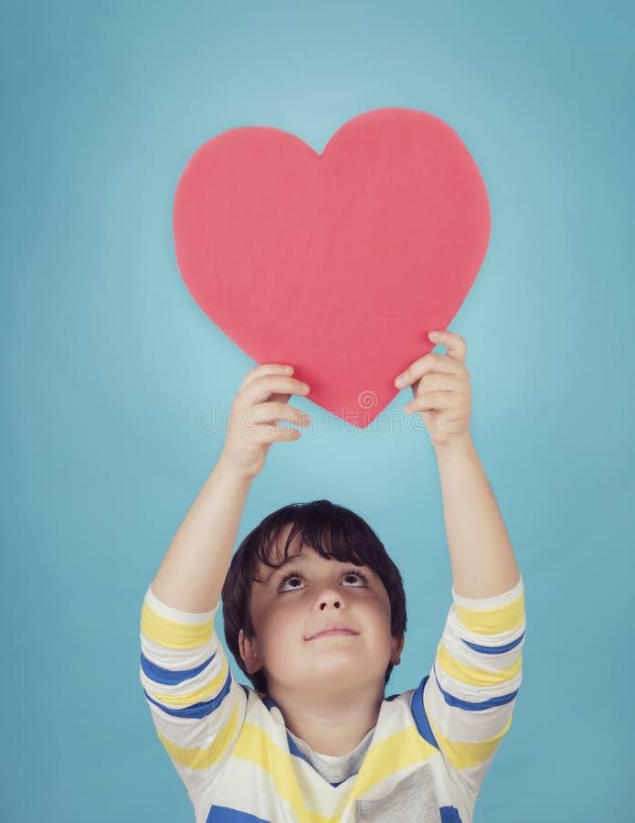 Le pojken med en hjärta arkivfoton