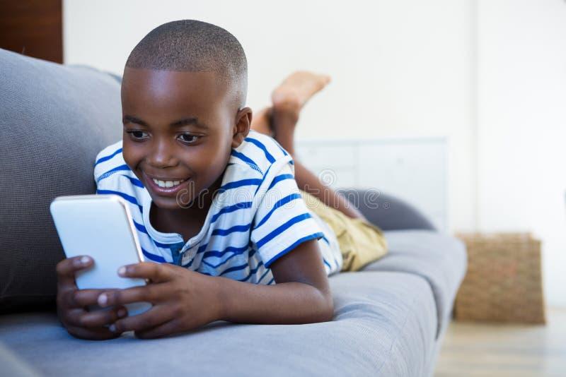 Le pojken som använder mobiltelefonen, medan ligga på soffan hemma arkivfoto