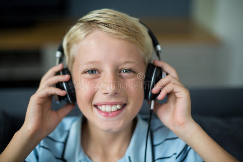 Le pojken som lyssnar till musik på hörlurar i vardagsrum royaltyfri foto