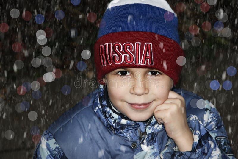 Le pojken som ser kameran under ett snöfall i en hatt Ryssland arkivfoto