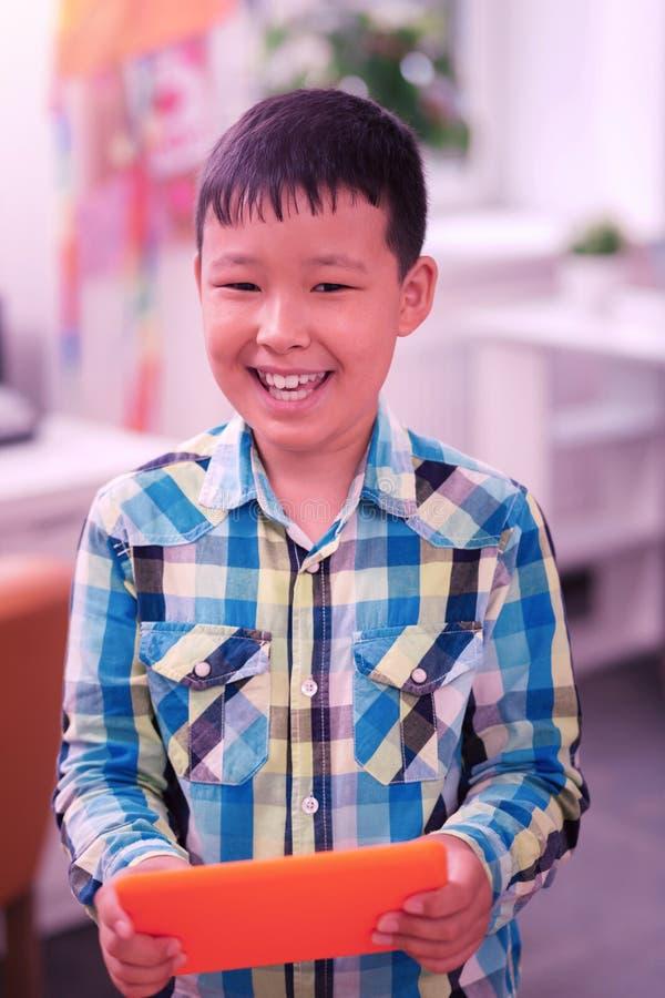 Le pojken som spelar med hans orange minnestavla arkivfoton