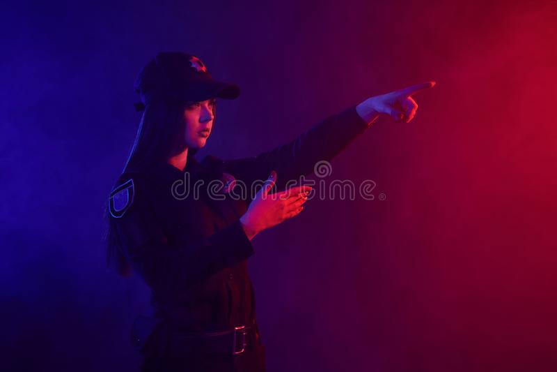 Le policier féminin de roux pose pour la caméra sur un fond noir avec le contre-jour rouge et bleu photo stock
