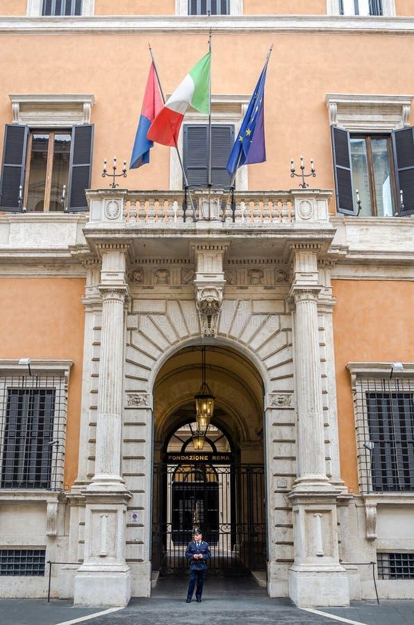 Le policier italien de carabiniere garde l'entrée à un établissement public dans un bâtiment historique à Rome avec les drapeaux  photos stock