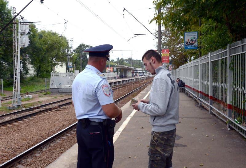 Le policier vérifie les documents du citoyen sur la plate-forme ferroviaire images libres de droits
