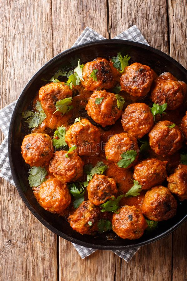 Le polpette indonesiane del pollo piccante vengono completo in un primo piano cremoso della salsa di curry della noce di cocco su immagini stock