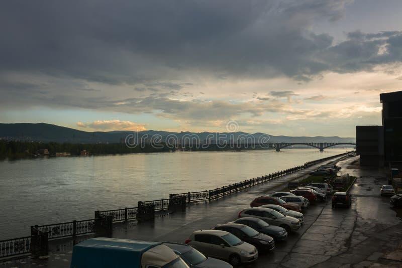 Le pont communal est une automobile et un pont piétonnier à travers le fleuve Ienisseï dans Krasnoïarsk, Russie Le remblai dessus photo libre de droits