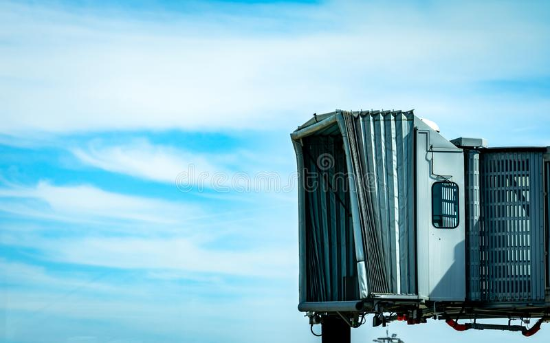 Le pont en jet apr?s ligne a?rienne commerciale d?collent ? l'a?roport contre le ciel bleu et les nuages blancs Pont d'embarqueme photographie stock libre de droits