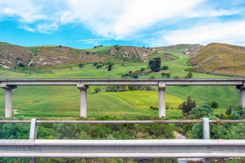 Le pont en route de route, viaduc soutient dans la vallée parmi les collines vertes, infrastructure de transport photo libre de droits