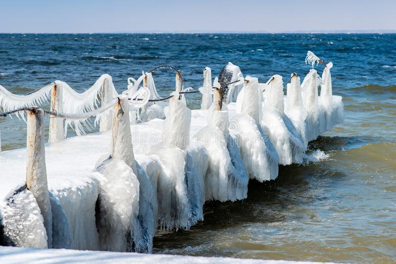 Le pont, situé sur la mer, est couvert de la glace Glaçons pendant de l'eau rugueuse images libres de droits