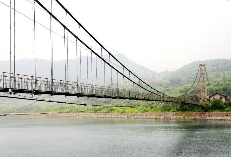 Le pont suspendu sur le royaume des fées brumeux de la rivière de Dongjiang photographie stock
