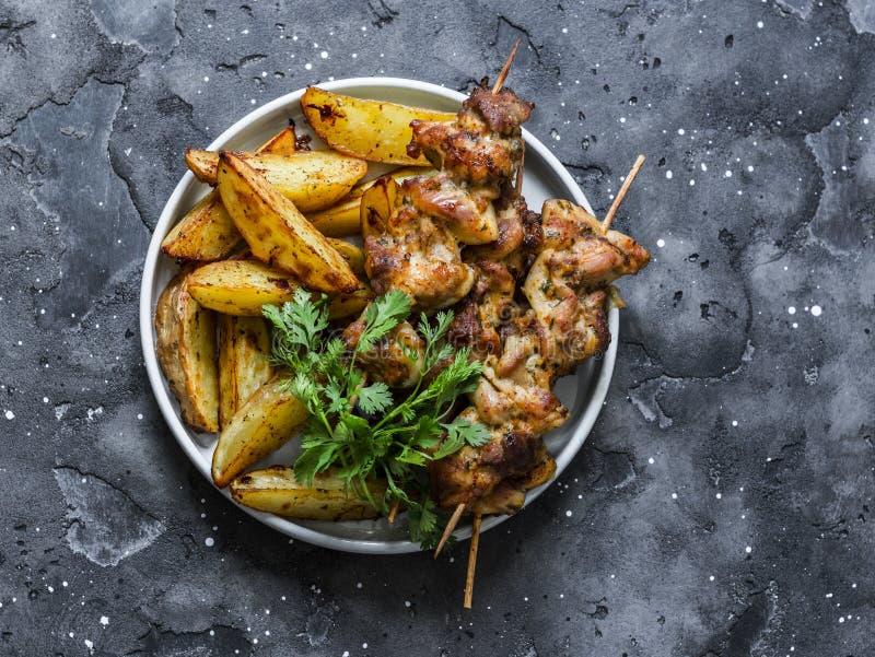 Le porc embroche le chiche-kebab avec les pommes de terre cuites au four sur un fond foncé, vue supérieure Tapas d?licieux images stock