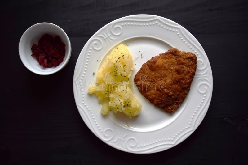 Le porc a fait frire l'escalope de veau avec la pomme de terre sur la table en bois noire Schnitzel de saucisse images libres de droits