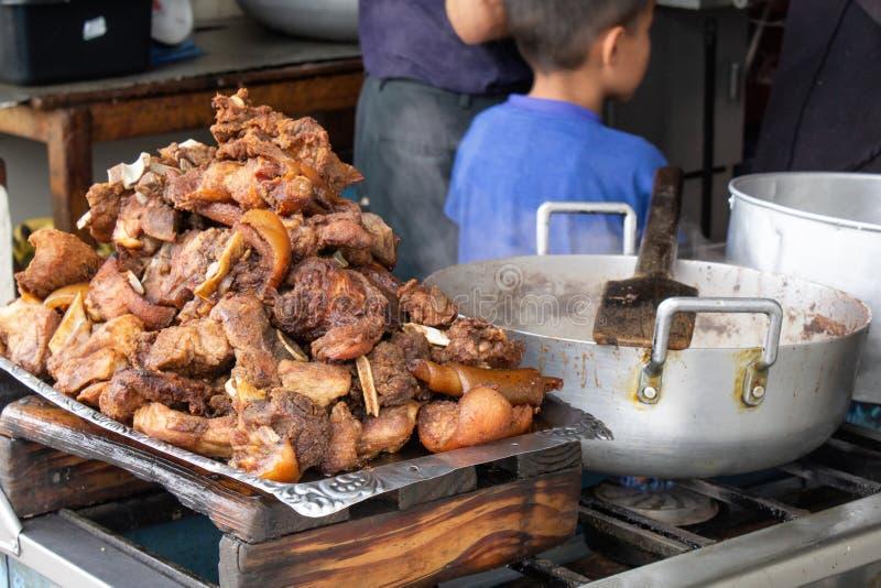 Le porc frit, frit sur la rue dans une cuve est le plat national des Indiens en Amérique du Sud photos libres de droits