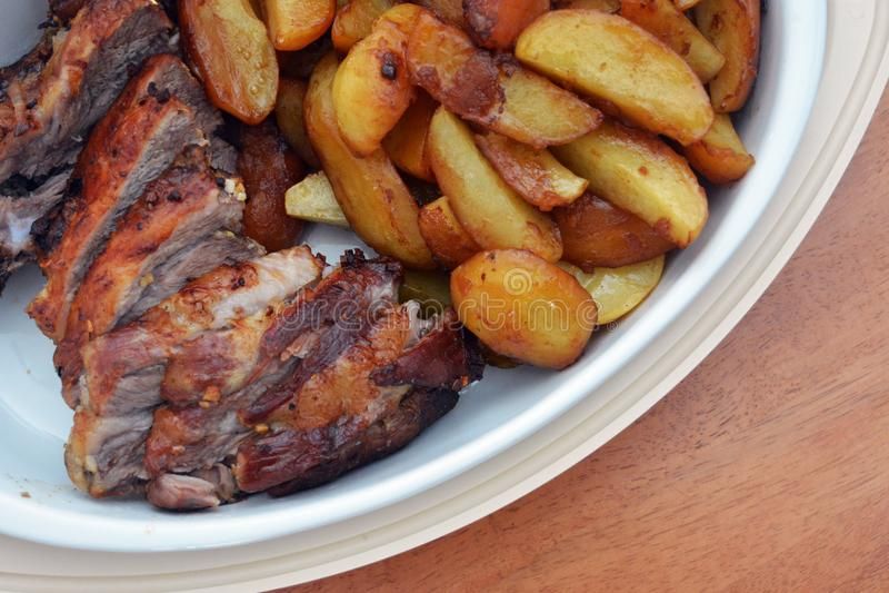 Le porc rôti et les pommes de terre cuites au four images libres de droits