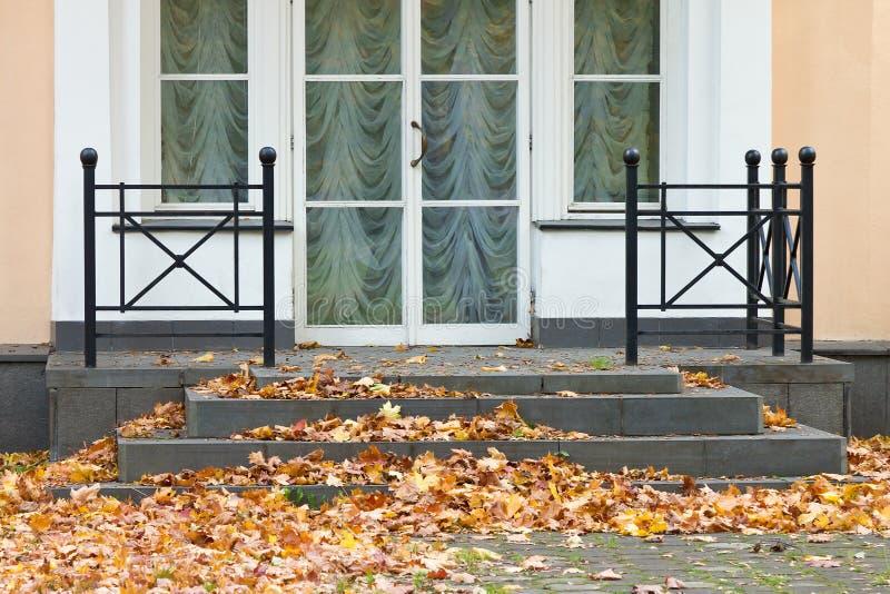 Le porche du bâtiment, clouté avec les feuilles d'automne tombées image libre de droits