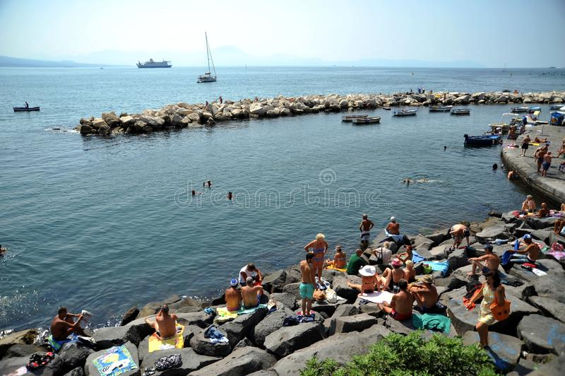 Le port de Naples avec des bateaux et des personnes sur les roches, Italie photo libre de droits