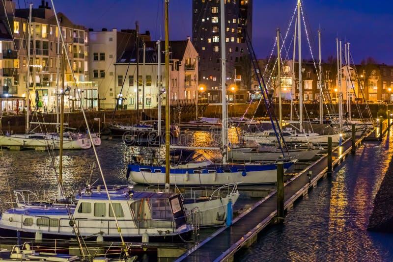 Le port du vlissingen la nuit avec beaucoup de bateaux accouplés, bateaux décorés avec les lumières, bâtiments allumés de ville a photographie stock