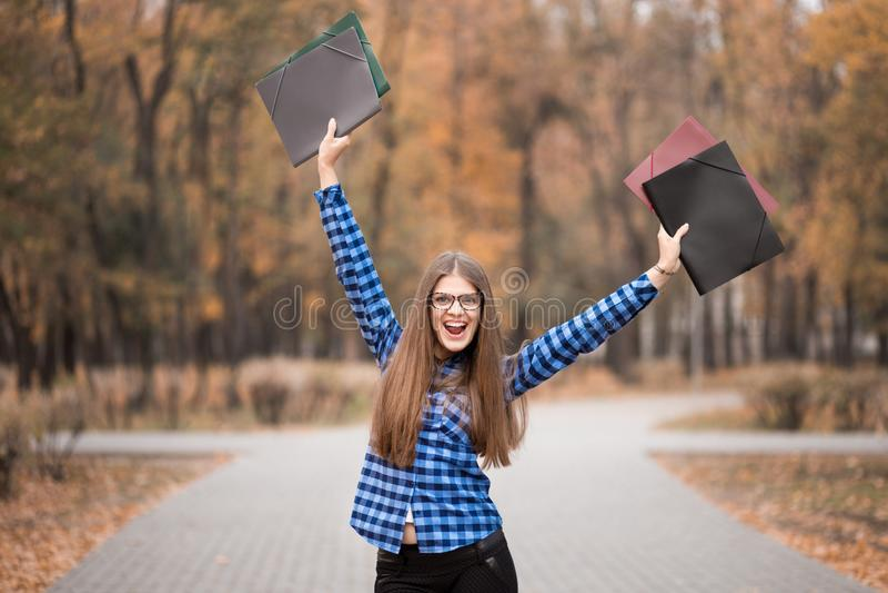 Le port euphorique de fille de gagnant dans la chemise bleue, grandes choses se sentantes sur le chemin de carrière, travaillant  image libre de droits