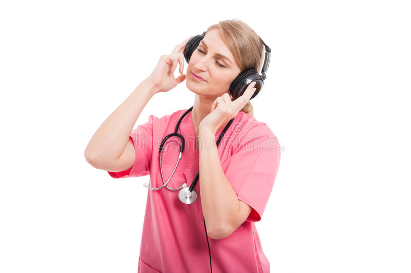 Le port femelle d'infirmière frotte apprécier la musique de écoute photo libre de droits