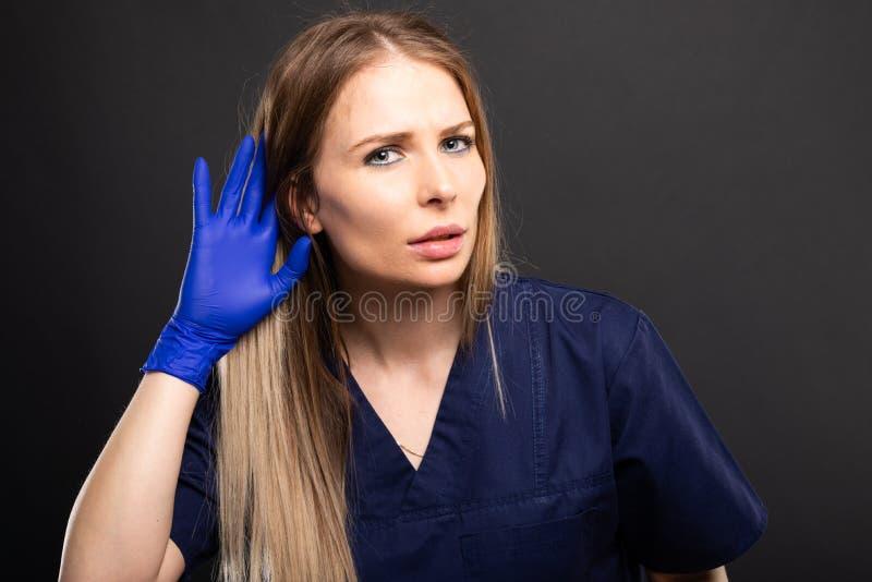 Le port femelle de docteur frotte faire le geste d'audition photo stock