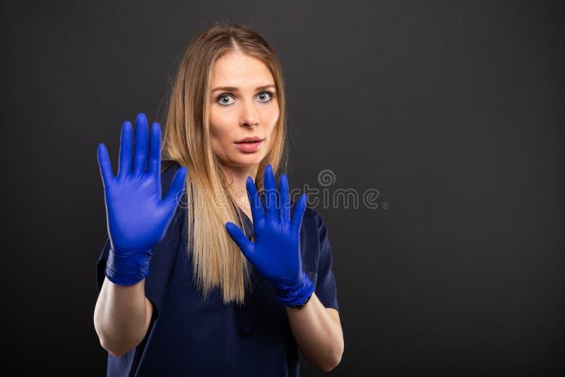 Le port femelle de docteur frotte faire le geste effrayé image stock