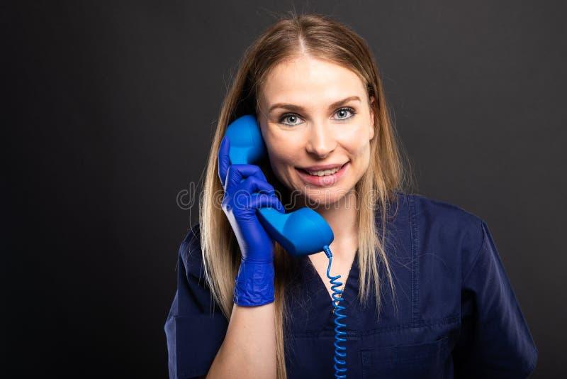 Le port femelle de docteur frotte parler au récepteur téléphonique bleu images stock
