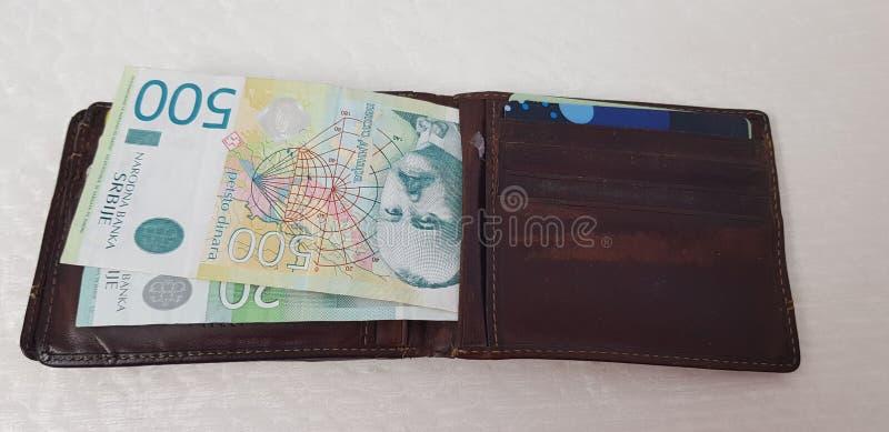 Le portefeuille avec des cartes de crédit et la monnaie fiduciaire serbe s'étendent sur la table blanche photos libres de droits