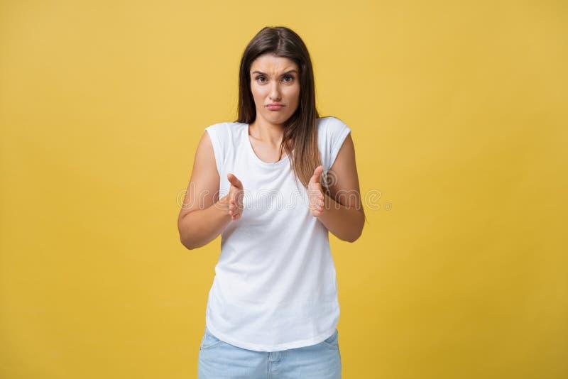 Le portrait a déçu la femme attirante maladroite dans la chemise blanche, soulevant la main et formant le petit article, regardan photographie stock
