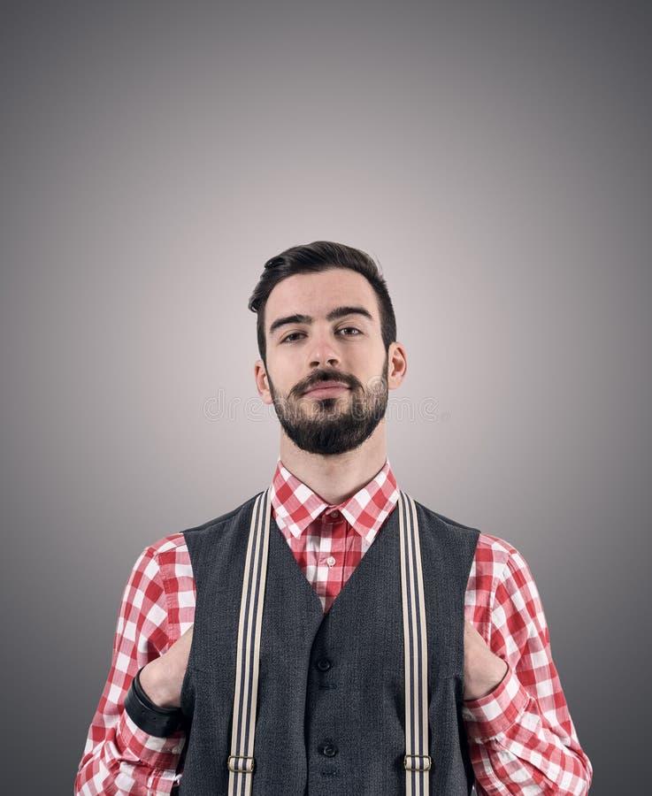 Le portrait désaturé du jeune hippie barbu avec des mains a enfoncé son gilet photos libres de droits