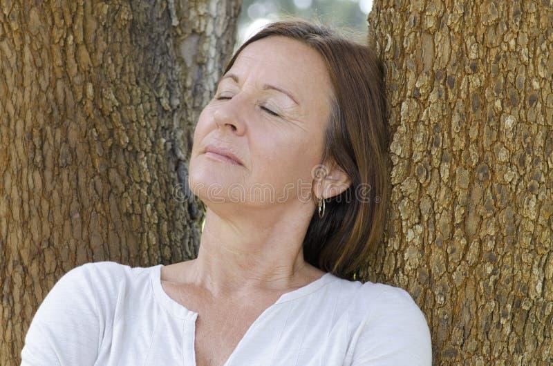 Yeux fermés relaxed de femme mûre extérieurs photo stock