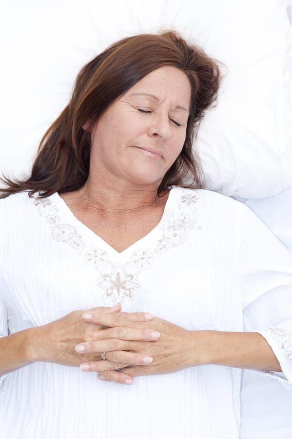 Femme mûre de sourire endormie dans le lit photo libre de droits
