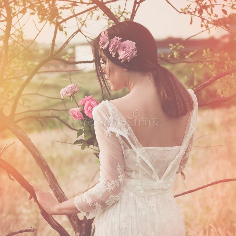 Le portrait d'été de la jeune femme dans la robe blanche tenant des fleurs se tiennent prêt l'arbre, tir arrière photo libre de droits