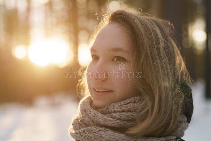 Le portrait d'adolescente dans la forêt de pin d'hiver est coucher du soleil photographie stock libre de droits
