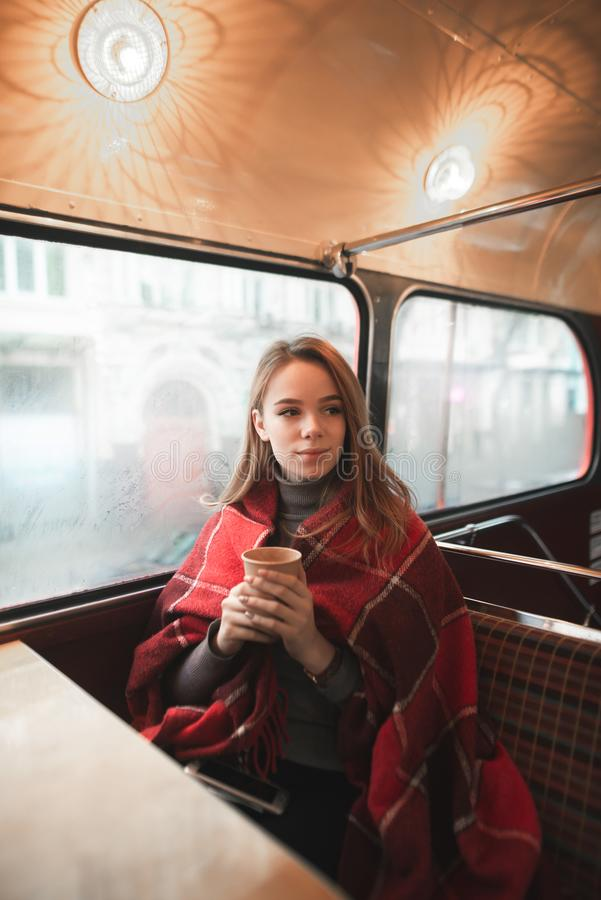 Le portrait d'hiver d'une jeune fille, couvert de couverture, se repose avec une tasse de café près de la fenêtre et de regards a photo stock