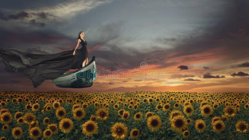Le portrait d'imagination de la jeune femme dans la robe noire sur le bateau au-dessus des tournesols mettent en place images stock