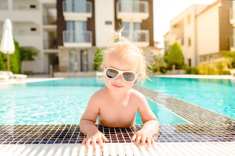 Le portrait d'un bébé blond dans des lunettes de soleil, sortir de la piscine photographie stock libre de droits