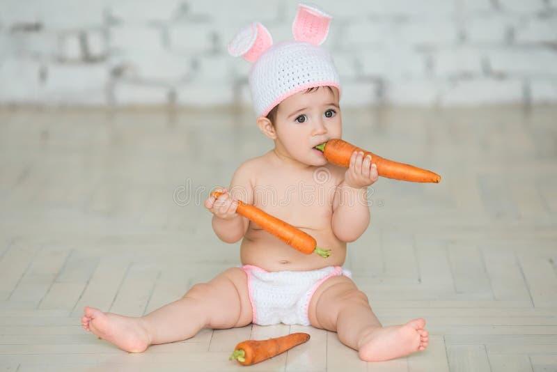 Le portrait d'un bébé mignon s'est habillé dans des oreilles de lapin de Pâques se reposant et photos libres de droits